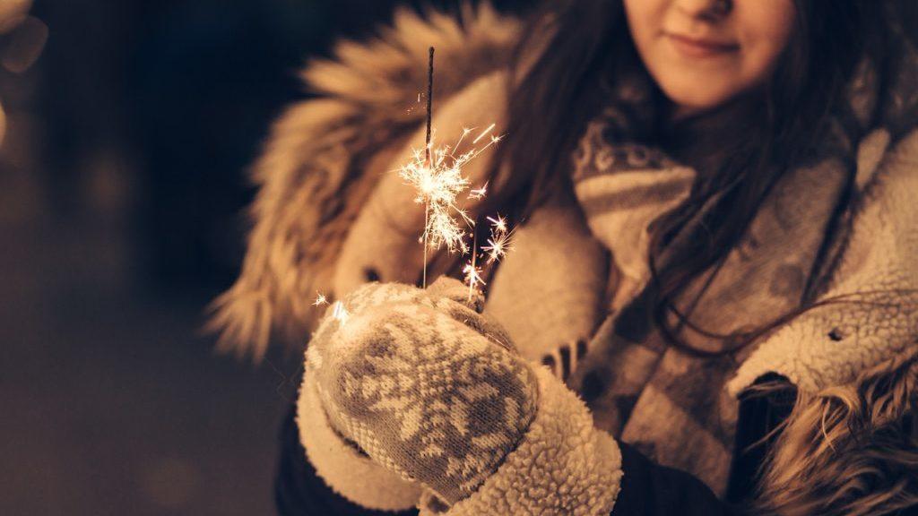 コートを着た花火を持つ女性